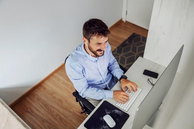 Draufsicht des innovativen hübschen bärtigen geschäftsmannes, der in seinem hauptbüro sitzt und an wichtigem projekt arbeitet.