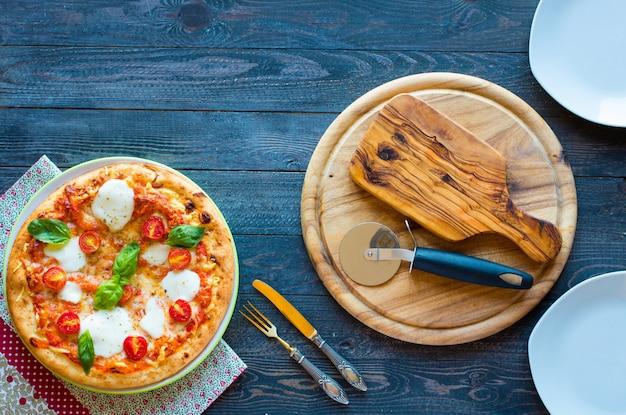 Draufsicht des italienischen klassischen pizza margherita über einem holztisch mit belägen