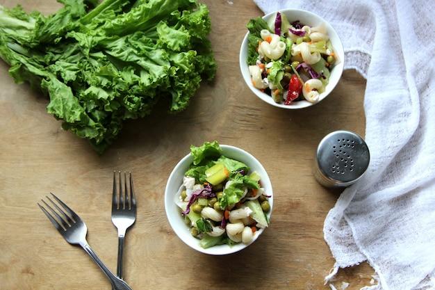 Draufsicht des italienischen nudelsalats mit frischem tomatenkäsesalat und eingelegten oliven in einer schüssel