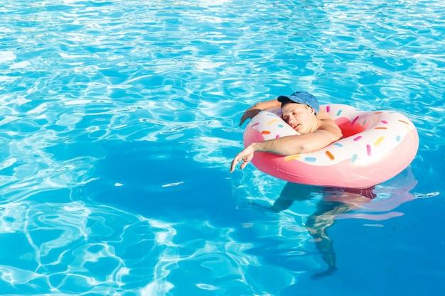 Draufsicht des jungen betrunkenen kerlschwimmens mit rosa kreis im pool.