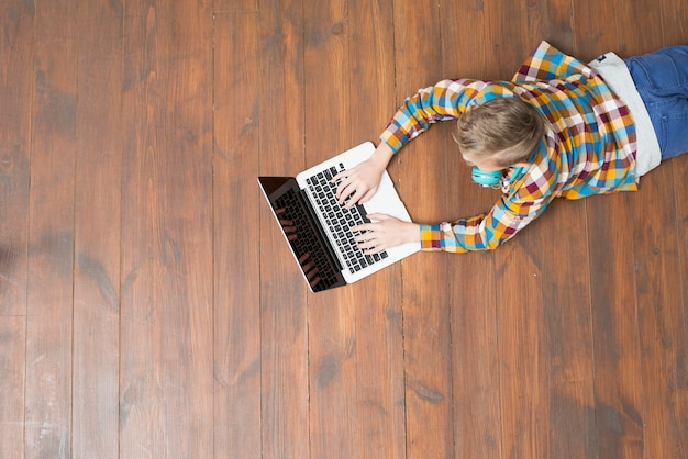 Draufsicht des jungen, der laptop verwendet