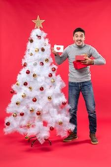 Draufsicht des jungen erwachsenen in einer grauen bluse, die nahe dem geschmückten weißen weihnachtsbaum steht und seine geschenke hält