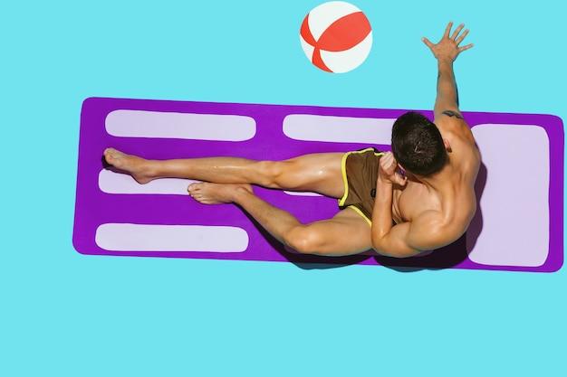 Draufsicht des jungen kaukasischen männlichen modells, das auf strandresort auf lila matte ruht