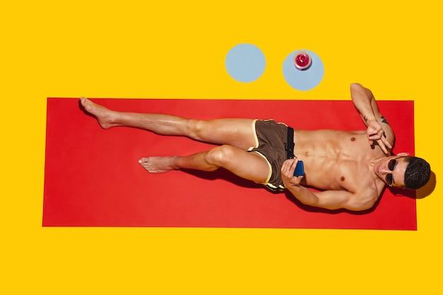Draufsicht des jungen kaukasischen männlichen modells, das auf strandresort auf roter matte und gelbem ruht