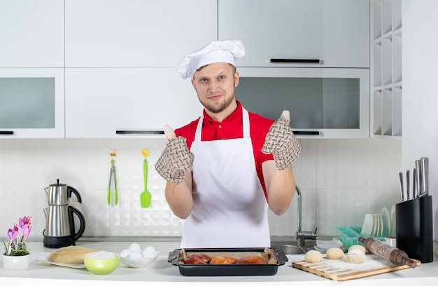 Draufsicht des jungen kochs, der einen halter trägt, der hinter dem tisch mit gebäck-eierreibe steht und in der weißen küche eine gute geste macht