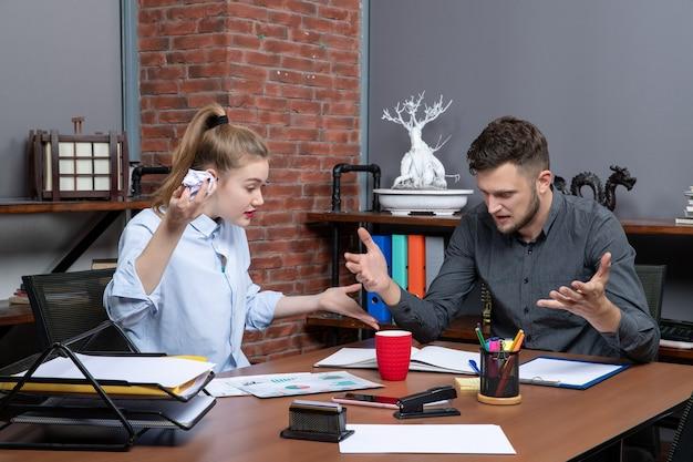 Draufsicht des jungen lustigen büroteams, das bei einem problem in der büroumgebung verwirrt ist