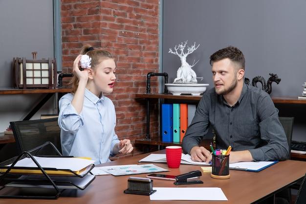 Draufsicht des jungen lustigen büroteams, das seine pausenzeit in der büroumgebung genießt