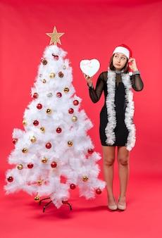 Draufsicht des jungen mädchens in einem schwarzen kleid mit weihnachtsmannhut, der nahe weihnachtsbaum steht und herz auf rot hält
