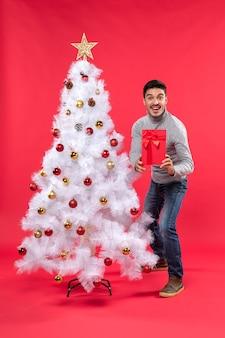 Draufsicht des jungen mannes, der nahe dem geschmückten weißen neujahrsbaum steht und seine geschenke hält und es seinen freunden auf rot zeigt