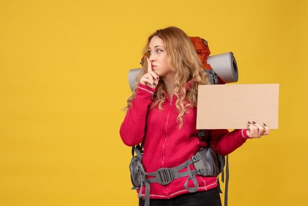 Draufsicht des jungen überraschten reisenden mädchens, das ihr gesamtes gepäck sammelt und freien platz zum schreiben zeigt, das stille geste macht