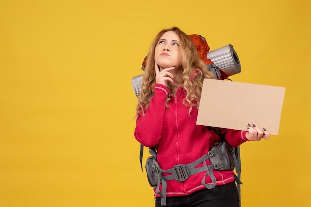 Draufsicht des jungen überraschten reisenden mädchens, das ihr stehendes gepäck sammelt