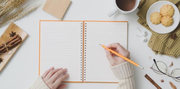 Draufsicht des jungen weiblichen schreibens auf notizbuch im herbstarbeitsplatz