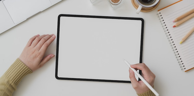 Draufsicht des jungen weiblichen schreibens auf tablette des leeren bildschirms beim arbeiten an ihrem projekt