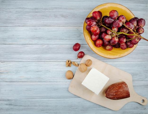 Draufsicht des käses, der geräuchert wird und feta-käse auf einem hölzernen schneidebrett mit walnüssen und süßer traube in einem teller auf rustikalem tisch mit kopienraum
