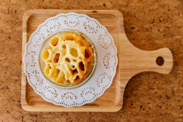 Draufsicht des käses gebackenes penne in der glasschüssel auf hölzerner platte mit salz, pfeffer und tischbesteck.