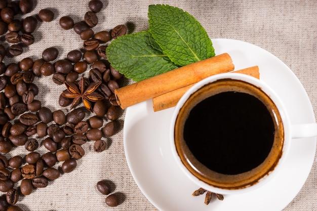 Draufsicht des kaffees im becher durch bohnenhaufen