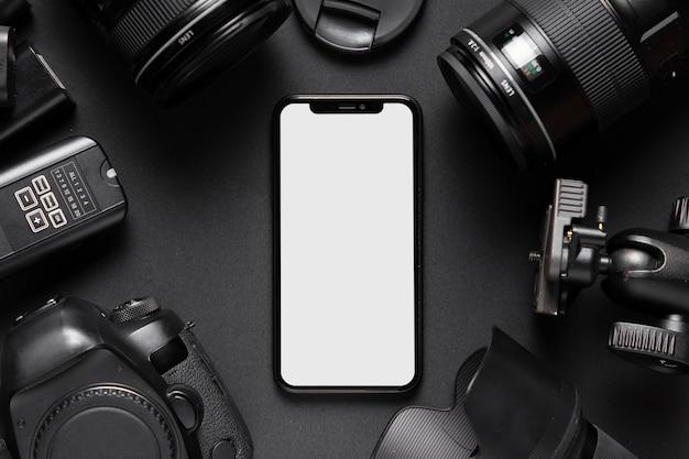 Draufsicht des kamerazubehörs und des smartphone auf schwarzem hintergrund