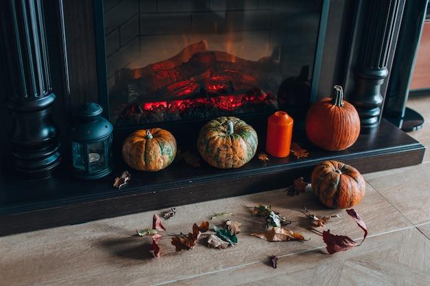 Draufsicht des kamins verziert mit kürbisen und trockenem herbstlaub und orange kerze. gemütliches zuhause konzept. vorbereitung auf halloween.