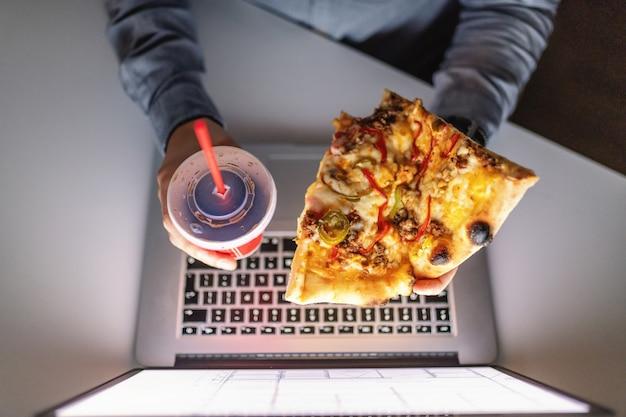 Draufsicht des kaukasischen fleißigen mannes, der pizza und tasse mit saft über laptop hält