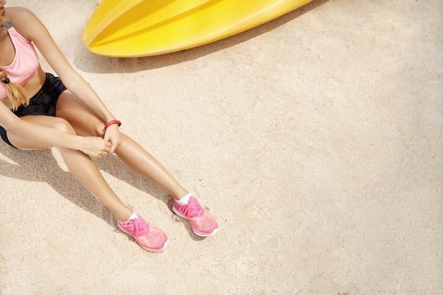 Draufsicht des kaukasischen frauenläufers in der sportbekleidung, die am strand nach aktivem training am meer sitzt. sportlerin in rosa laufschuhen hält den atem an, während sie sich während des trainings auf sand ausruht