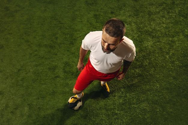 Draufsicht des kaukasischen fußball- oder fußballspielers auf grünem hintergrund des grases. junges männliches sportliches modelltraining, übend. ball treten, angreifen, fangen. konzept des sports, des wettbewerbs, des gewinnens.