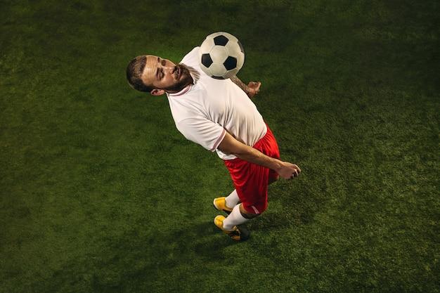 Draufsicht des kaukasischen fußball- oder fußballspielers auf grüner graswand.