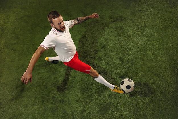 Draufsicht des kaukasischen fußballs oder des fußballspielers auf grün