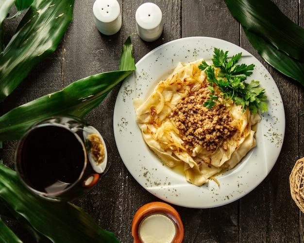 Draufsicht des khangal-gerichts, das mit hackfleisch-zwiebel-mischung gekrönt wird