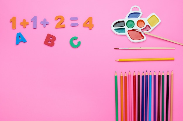 Draufsicht des kindertisches, die zusammensetzung der pinselbuchstabenzahlen farbstifte radiergummi verschiedene linie auf einem rosa hintergrund