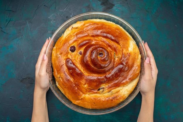 Draufsicht des kirschkuchens mit kirschen innerhalb halten durch weibliches auf dunkelblauem, süßem kuchenfruchtdunkel des kuchens