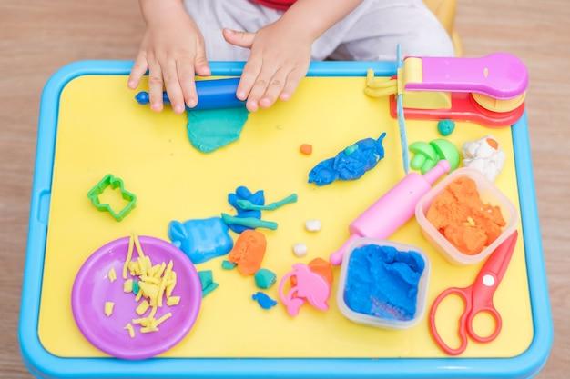 Draufsicht des kleinen asiatischen 2 jahre alten kleinkindbabys, das spaß daran hat, bunte modelliermasse zu spielen / dought zu spielen, spielzeug in der spielschule zu kochen, lernspielzeug kreatives spiel für kleinkindkonzept