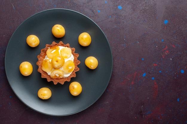 Draufsicht des kleinen cremigen kuchens mit frischen süßkirschen innerhalb der platte auf der dunklen oberfläche