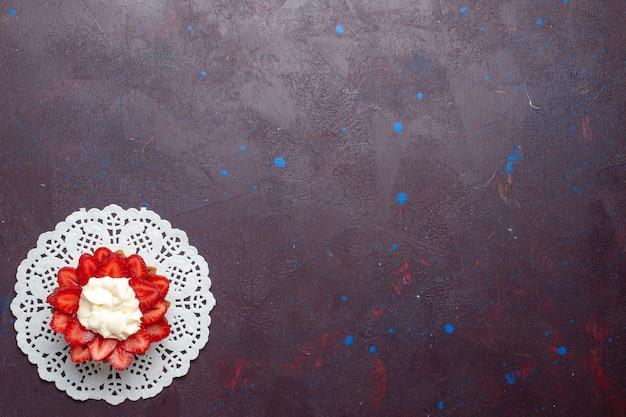 Draufsicht des kleinen cremigen kuchens mit geschnittenen früchten auf der dunklen oberfläche