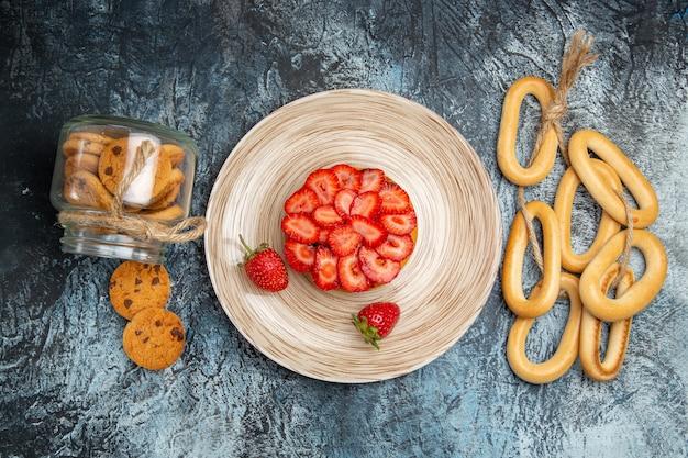 Draufsicht des kleinen fruchtigen kuchens mit crackern auf dunkler oberfläche
