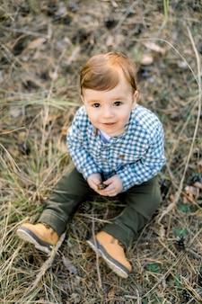 Draufsicht des kleinen jungen im karierten hemd, im herbstkiefernwald sitzend, mit kegel spielend und zur kamera lächelnd