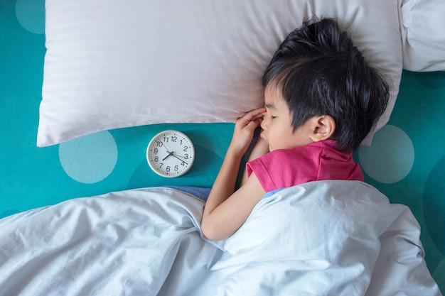 Draufsicht des kleinen jungen schlafend auf bett mit wecker nahe seinem kopf.