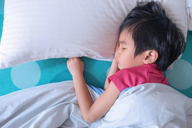 Draufsicht des kleinen jungen schlafend auf bett