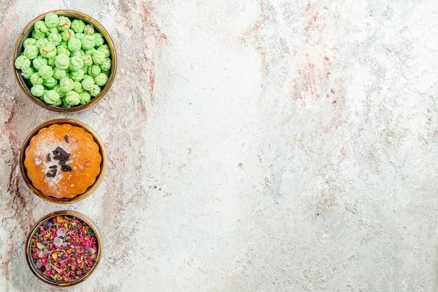 Draufsicht des kleinen kuchens mit bonbons auf weiß on