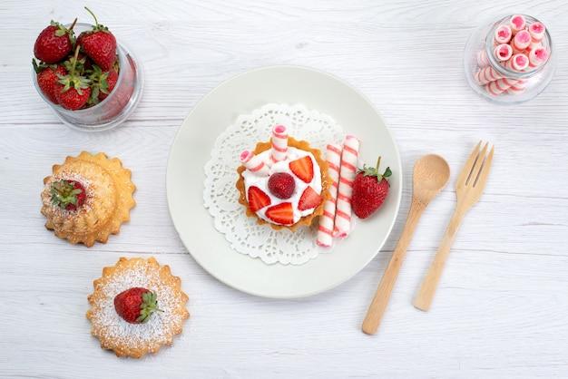 Draufsicht des kleinen kuchens mit sahne und geschnittenen erdbeerkuchen-bonbons auf weißem obstkuchen-beeren-süßem