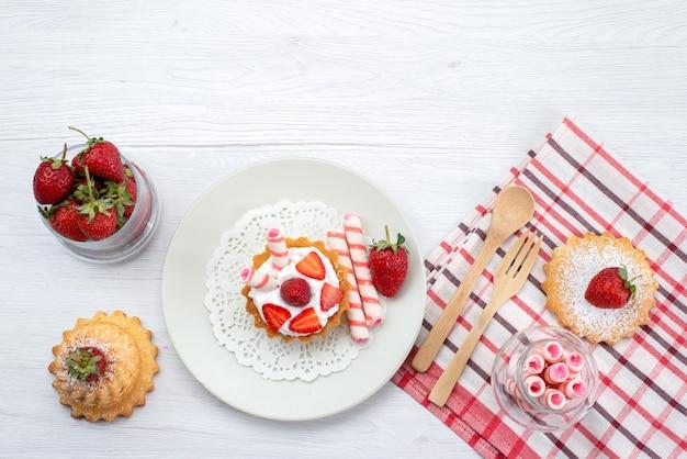 Draufsicht des kleinen kuchens mit sahne und geschnittenen erdbeerkuchen-bonbons auf weißem schreibtisch, süßem zucker der obstkuchenbeere