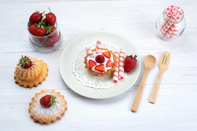 Draufsicht des kleinen kuchens mit sahne und geschnittenen erdbeerkuchen-bonbons auf weißem, süßem obstkuchen-beerenzucker