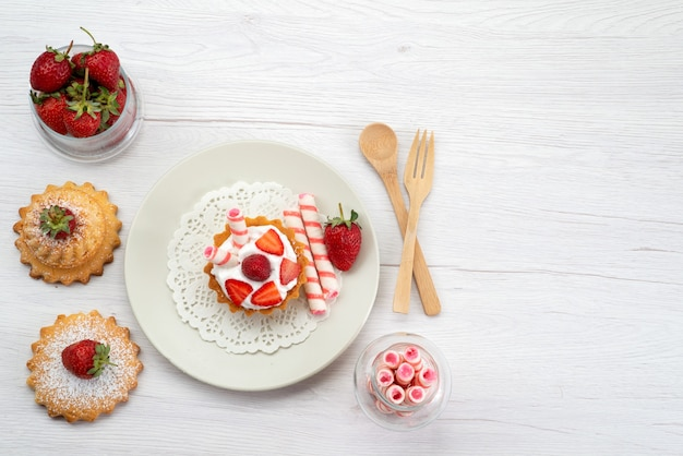 Draufsicht des kleinen kuchens mit sahne und geschnittenen erdbeerkuchen-bonbons auf weißem süßem zucker des obstkuchens