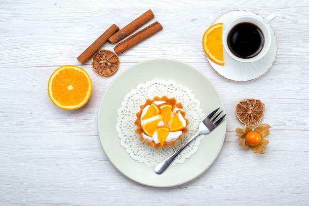 Draufsicht des kleinen kuchens mit sahne und geschnittenen orangen zusammen mit kaffee und zimt auf hellem schreibtisch, süßem zucker des obstkuchenplätzchens