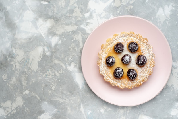 Draufsicht des kleinen kuchens mit zuckerpulver und früchten auf dem leichten fruchtbeerenkuchen backen kuchen