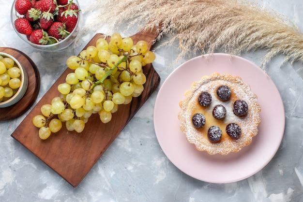 Draufsicht des kleinen kuchens mit zuckerpulverfrüchten zusammen mit frischen roten erdbeeren und trauben auf leichtem süßem tee des obstkuchenbackens