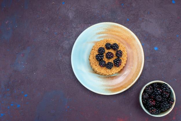 Draufsicht des kleinen runden kuchens mit beeren innerhalb platte auf dunkler oberfläche