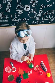 Draufsicht des kleinen wissenschaftlers, der mit chemischen flüssigkeiten über dem tisch gegen die tafel mit zeichnungen spielt