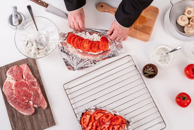 Draufsicht des kochs, der gericht mit fleisch und tomaten zubereitet