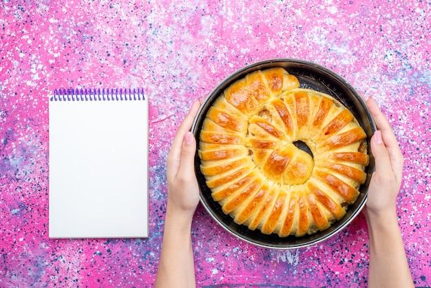 Draufsicht des köstlichen armreifs des gebackenen gebäcks gebildet innerhalb der pfanne mit notizblock auf hellem schreibtisch, süßer zucker des kekskeksteigs des gebäcks