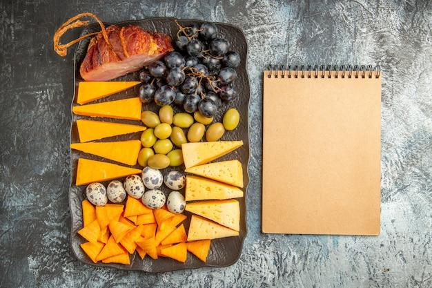 Draufsicht des köstlichen besten snacks für wein auf braunem tablett und notizbuch auf eishintergrund